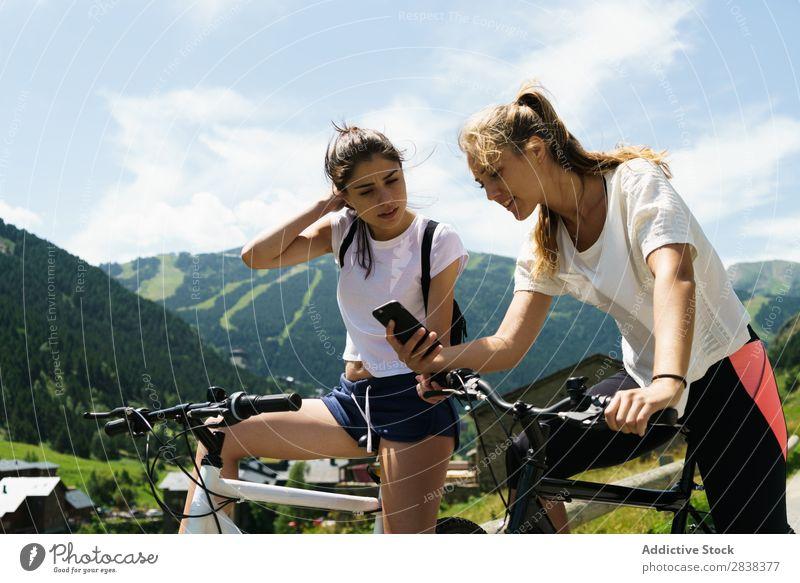 Frauen, die Smartphones auf Fahrrädern benutzen. Fahrrad PDA benutzend Freundschaft sportlich Sport Zyklus Mädchen Aktion Lifestyle Fahrradfahren Mensch