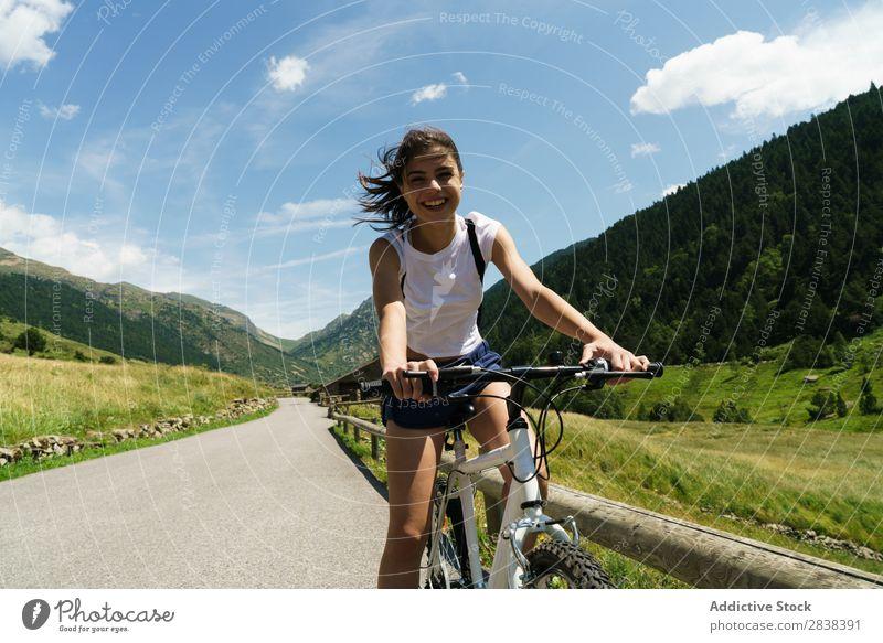 Frau auf dem Fahrrad mit Blick auf die Kamera sportlich heiter Lächeln Blick in die Kamera Sport Zyklus Mädchen Aktion Lifestyle Fahrradfahren Mensch Training