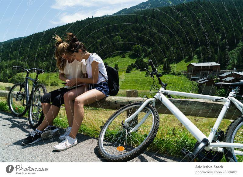 Frauen mit Fahrrädern beim Surfen im Smartphone sitzen Zaun PDA Browsen sportlich Fahrrad Freundschaft Sport Zyklus Mädchen Aktion Lifestyle Fahrradfahren