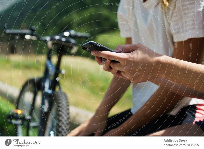 Schneiden Sie Frauen mit Fahrrädern, die auf dem Smartphone surfen. sitzen Zaun PDA Browsen sportlich Fahrrad Freundschaft Sport Zyklus Mädchen Aktion Lifestyle