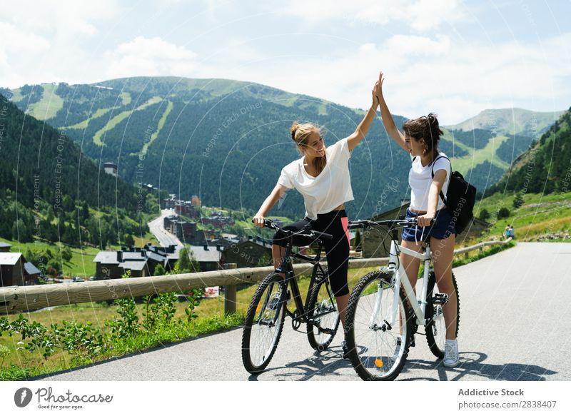 Frauen auf Fahrrädern, die High Five geben. sportlich Fahrrad high five Lächeln heiter Team Freundschaft Sport Zyklus Mädchen Aktion Lifestyle Fahrradfahren