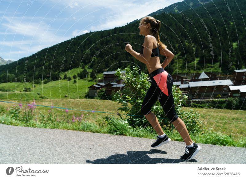 Frau beim Joggen auf dem Land Straße ländlich sportlich Jugendliche Fitness üben Athlet Sport Landschaft Training Freizeit & Hobby Aktion Sportbekleidung Gras