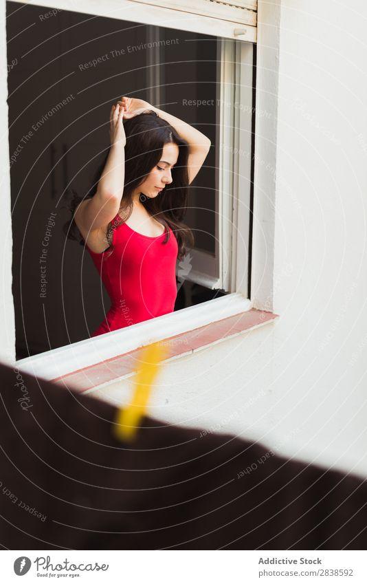 Sanftes Mädchen steht am Fenster. Frau zart genießen Model Raum elegant Erholung