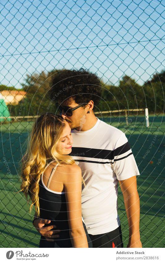 Paar, das auf dem Tennisplatz posiert. Körperhaltung sportlich Umarmen Freizeit & Hobby Sportbekleidung Fröhlichkeit Partnerschaft Team Freude Zusammensein