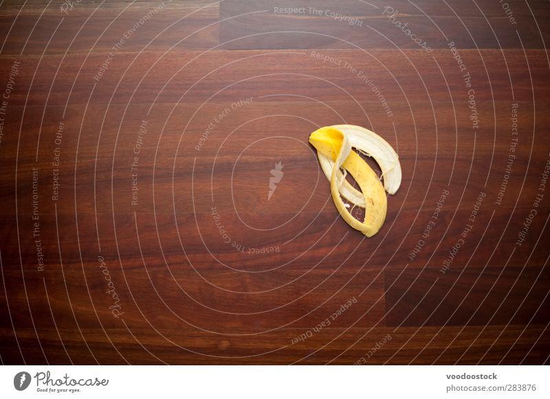 Einen Fehler oder Ausrutscher machen Frucht gelb Bananenschale Etage Oberfläche Holz unbedeutend sich[Akk] schälen Unfall Risiko potenzielle Gefahr Haut Unglück
