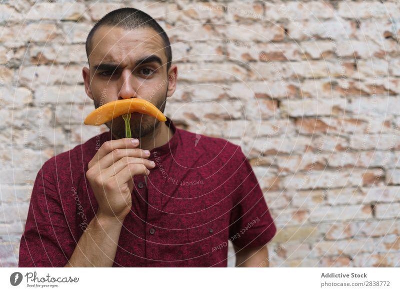 Verspielter Mann, der mit Früchten posiert. so tun, als ob spielerisch Oberlippenbart Spaß haben Frucht Nachbildung Körperhaltung Melonen Comic Humor Straße