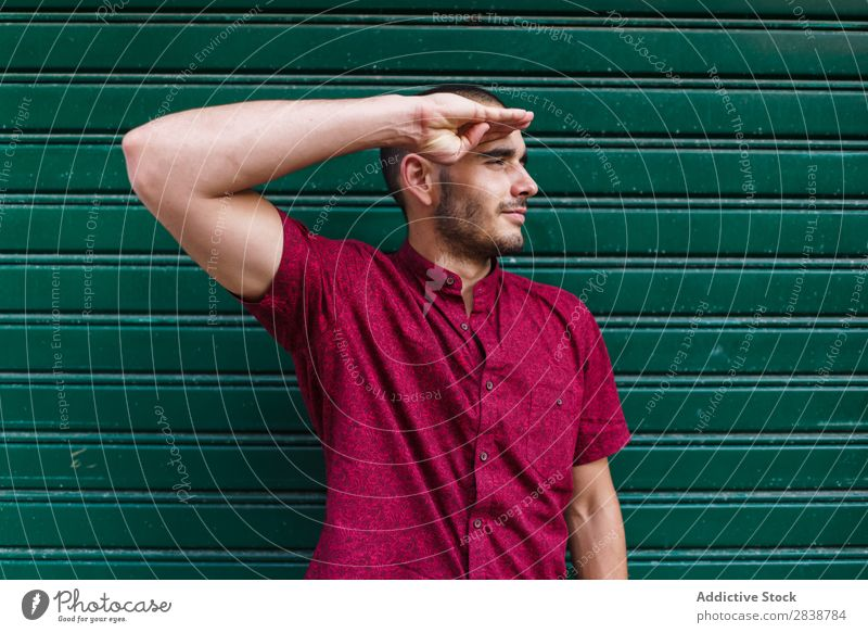 Lässiger Mann, der in der grünen Wand posiert. zeigen Muskulatur Ausdruck vortäuschend selbstbewußt Körperhaltung Stadt spielerisch Menschliches Gesicht lässig