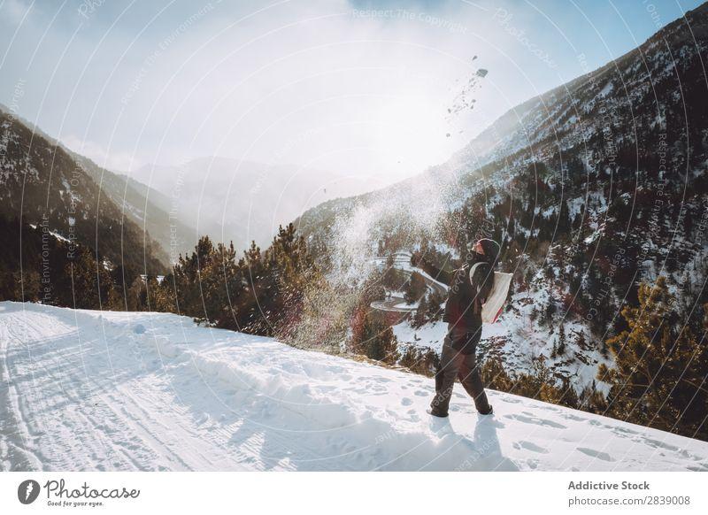 Mann, der Schnee wirft. Mensch Tourist Rucksack Winter Hügel Berge u. Gebirge Landschaft Natur weiß Eis Jahreszeiten kalt Ferien & Urlaub & Reisen Weg Frost