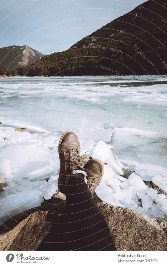 Touristische Entspannung am verschneiten Fluss Mensch Beine Eis Stein Winter Hügel Berge u. Gebirge