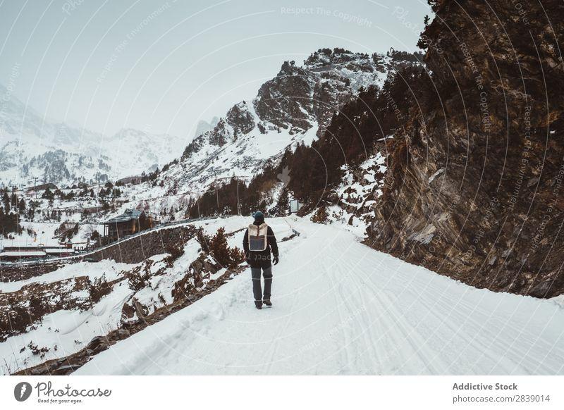 Mann, der auf einer verschneiten Straße geht. Winter Hügel Berge u. Gebirge Schnee Landschaft Natur weiß Eis Jahreszeiten kalt Ferien & Urlaub & Reisen Weg Wald