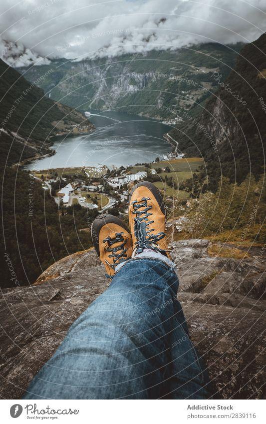 Getreideperson, die auf einer Klippe sitzt. Mensch Reisender Natur Ferien & Urlaub & Reisen Geirangerfjord Landschaft Aussicht Wohnsiedlung Tourismus Beine