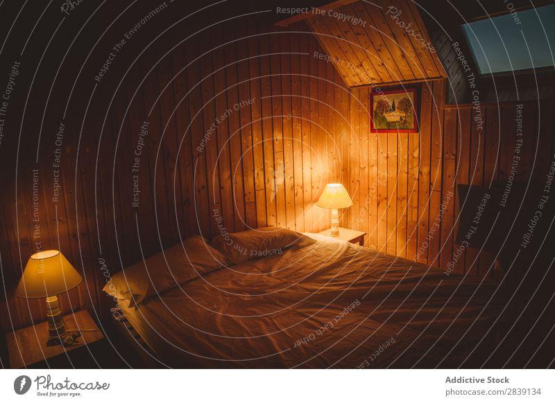 Schlafzimmerinnenraum mit brennenden Lampen Bett Innenarchitektur Wärme bequem Möbel heimwärts Wohnung Dekor Zeitgenosse Geborgenheit Licht Abend wohnbedingt