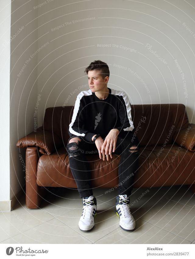 Junge Frau auf der Couch schaut heraus Lifestyle schön Wohlgefühl Wohnung Sofa Raum Jugendliche 18-30 Jahre Erwachsene Jeanshose Turnschuh brünett kurzhaarig