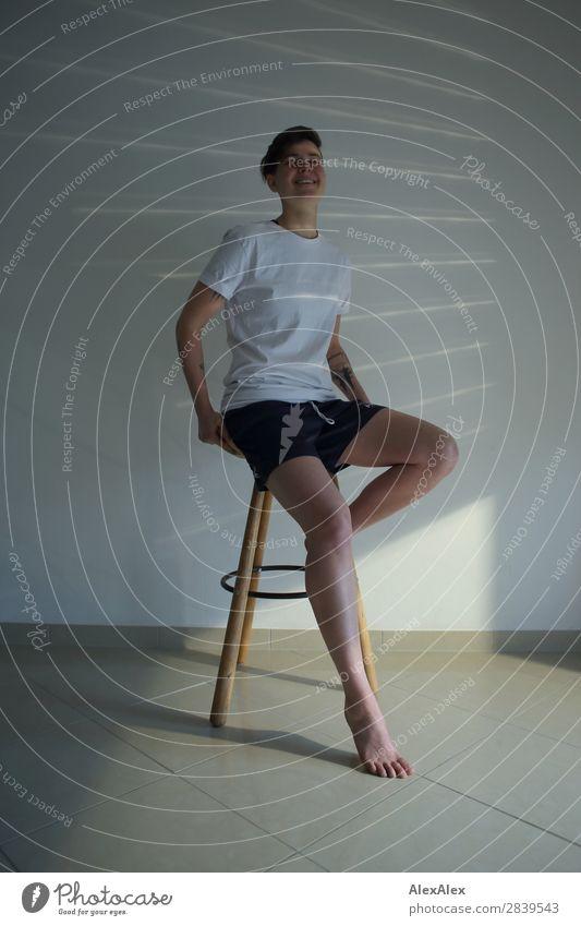 Junge Frau sitzt auf einem Hocker Stil schön Leben Wohnung Jugendliche Beine 18-30 Jahre Erwachsene T-Shirt Shorts Barfuß brünett kurzhaarig Lichtstreifen