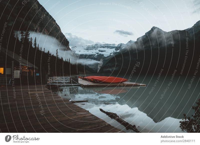 Ruhiger See am Hang Berge u. Gebirge Natur Aussicht Hügel Wasser Klippe Felsen Pflanze schön natürlich Jahreszeiten frisch Umwelt Wald mehrfarbig Licht