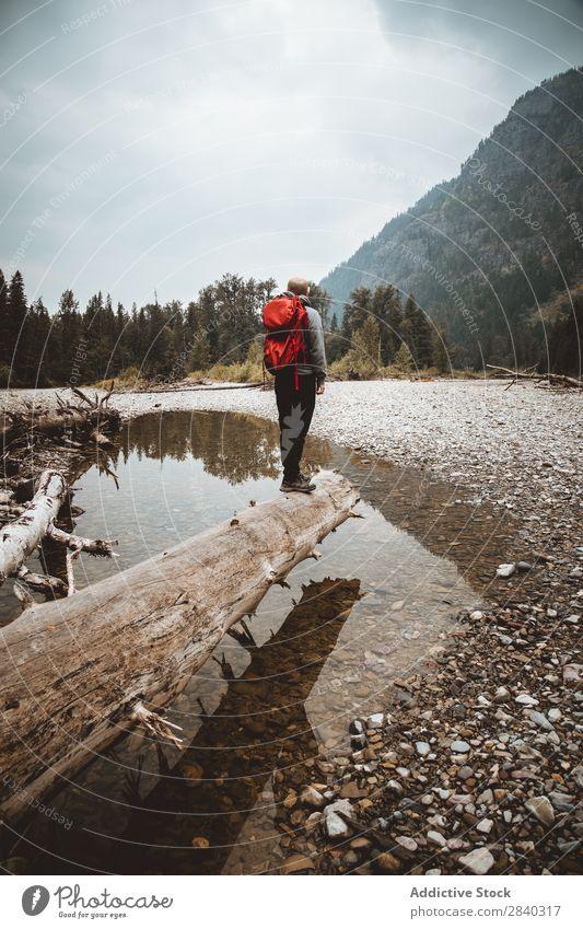 Reisender mit Rucksack, der in der Landschaft posiert. Mann Trekking Berge u. Gebirge wandern träumen nachdenklich Körperhaltung Wildnis Abenteurer Baumstamm