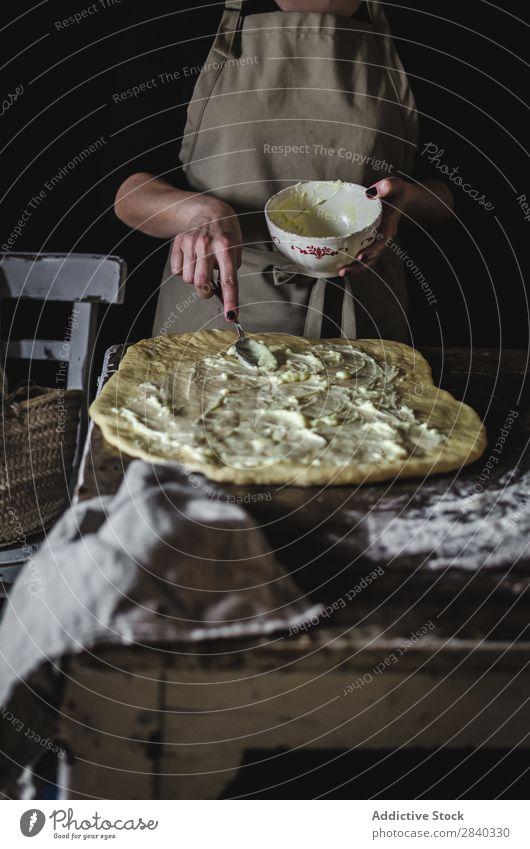 Frau, die die Füllung auf den Teig legt. Mensch kochen & garen Teigwaren kneten rustikal Mehl Lebensmittel Schalen & Schüsseln Putten Küchenchef Bäckerei