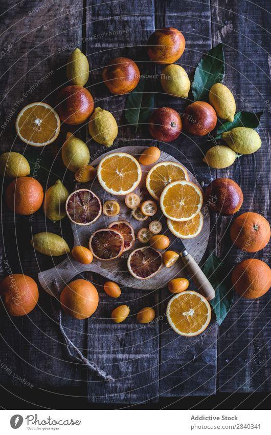 Geschnittene Zitrusfrüchte auf Holztisch Zitrone Orange rot frisch geschmackvoll Frucht Lebensmittel außergewöhnlich Sortiment Vielfalt Gesundheit gelb süß