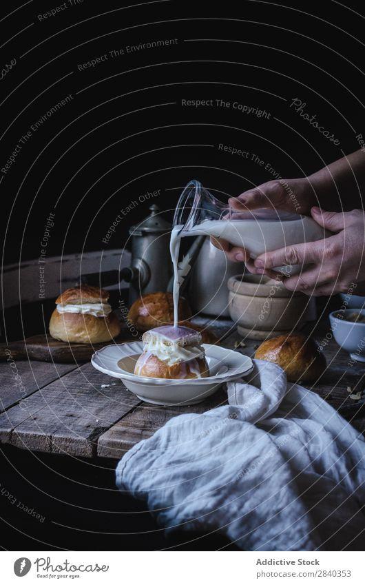 Hände gießen Milch auf Brötchen süß Backwaren rustikal lecker Hand Gießen Creme Portion Dessert Lebensmittel frisch geschmackvoll gebastelt Feinschmecker