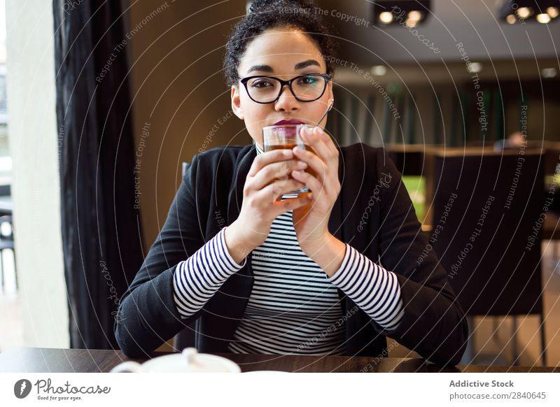 Schöne junge Frau, die Tee im Kaffee trinkt. trinken im Innenbereich Café Tisch attraktiv sitzen Getränk Vesper Pause Erwachsene Tasse Frühstück genießen