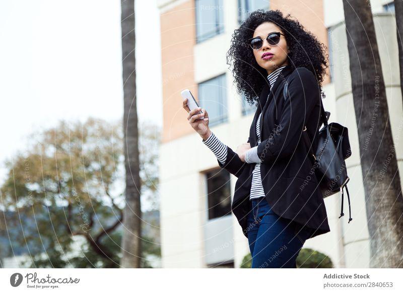 Schöne Frau, die ihr Handy auf der Straße benutzt. Mensch Jugendliche Telefon Freude Stadt Texten Internet urwüchsig Technik & Technologie Lächeln Glück