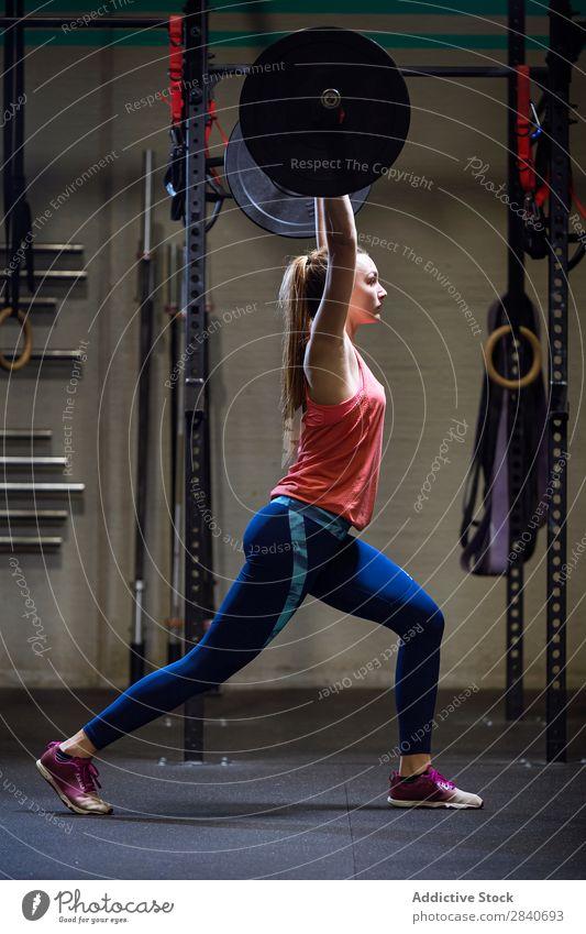 Sportliches Frauentraining mit Langhantel Sporthalle Training sportlich Fitness üben Curl-Hantel über Kopf Lifestyle Gesundheit Sportbekleidung Aktion Mensch