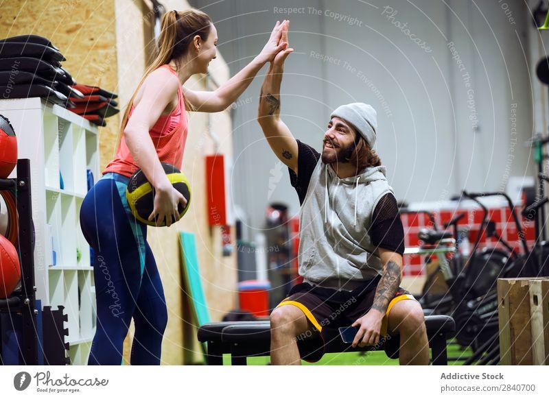 Sportliche Menschen, die sich im Fitnessstudio anfeuern. Sporthalle Training sportlich üben Lifestyle high five Applaus Gesundheit Sportbekleidung Aktion schön
