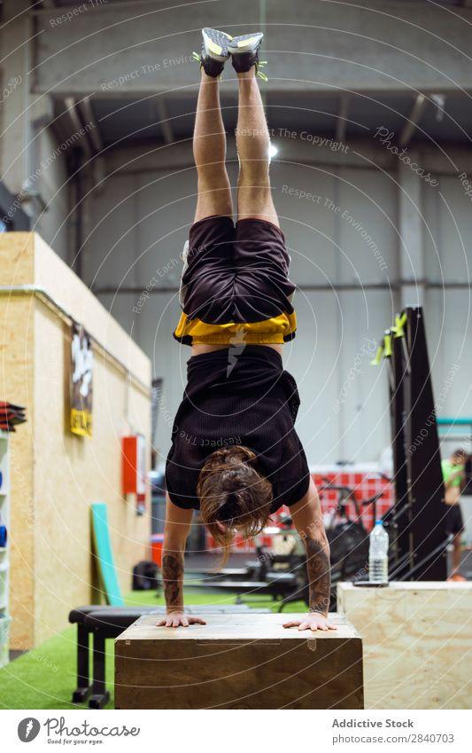 Mann steht kopfüber im Fitnessstudio. Sporthalle Training sportlich üben Lifestyle auf den Kopf gestellt auf Händen stehen Gesundheit Sportbekleidung Aktion