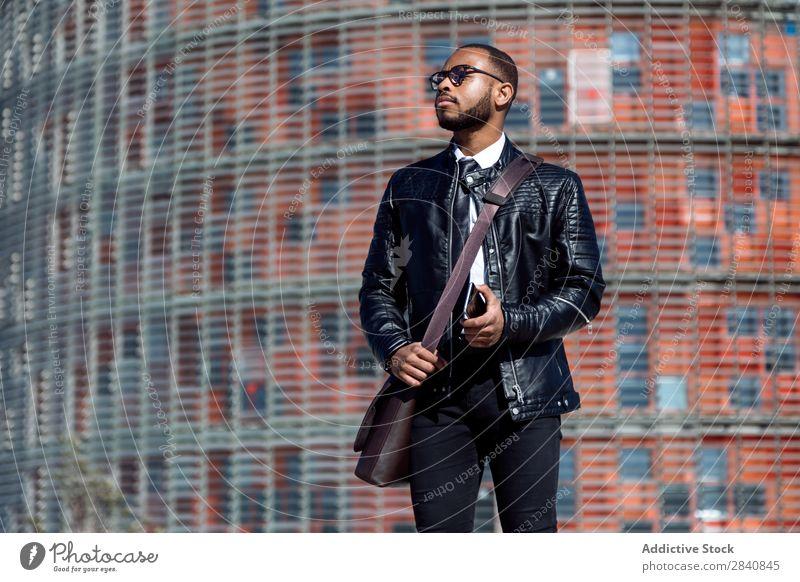 Modischer Mann in schwarzem Ledermantel und Brille, der sein Smartphone hält und auf den städtischen Hintergrund schaut. männlich gelungen Telefon stylisch