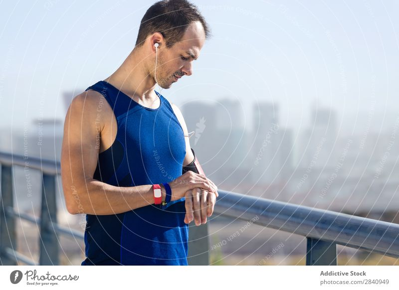 Der Läufer schaut auf seinen Puls mit Smartwatch. beobachten rennen Sport Zeit bewerten Bildschirm Mann Fitness Herz Training Gesundheit Sprint Joggen Sprinten