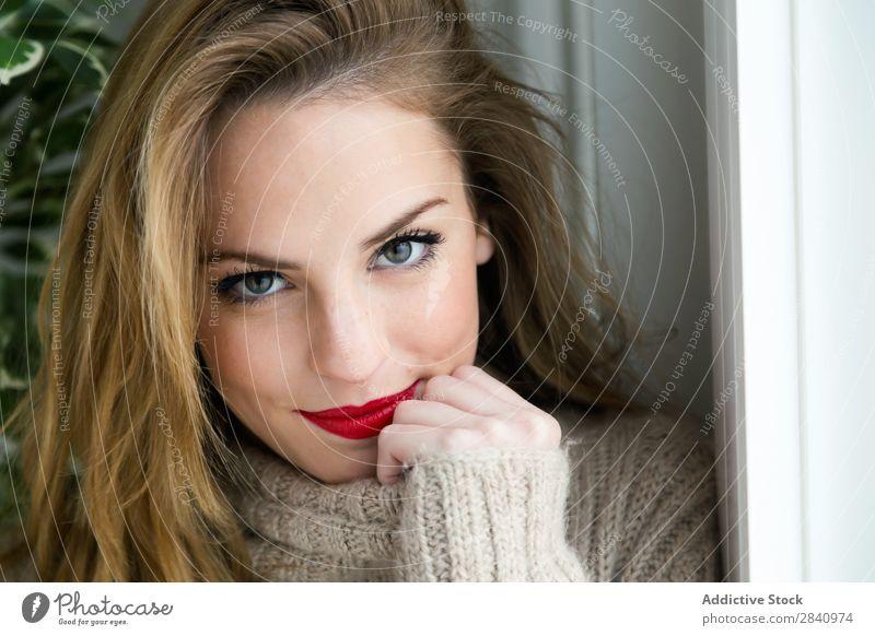 Schöne junge Frau, die zu Hause vor der Kamera steht. blond Auge rot Lippen Jugendliche Erwachsene Pullover im Innenbereich heimwärts Mädchen Lächeln nur 1