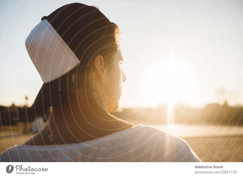 Chico Parkour Mann selbstbewußt bewundernd Sonnenuntergang Stadt Coolness sportlich hintergrundbeleuchtet Porträt Jugendliche Mode Stil modern gutaussehend weiß