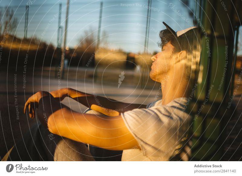 Chico Parkour Mann sitzen Raster selbstbewußt Stadt Coolness sportlich Porträt Jugendliche Mode Stil modern gutaussehend weiß lässig Bekleidung ernst
