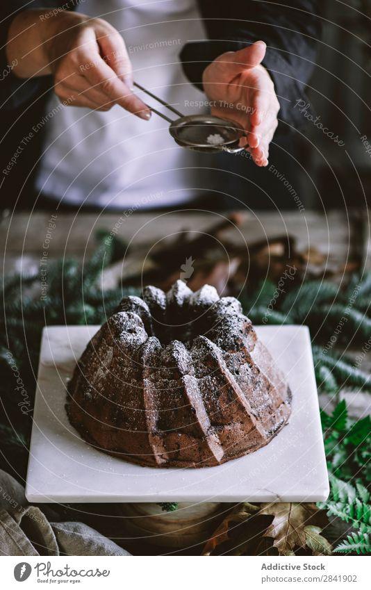 Getreideperson Puddingkuchen mit Puderzucker pflanzen. Mensch Kuchen Schokolade gepulvert Zucker Staubwischen Berieselung stehen Dessert süß Lebensmittel lecker