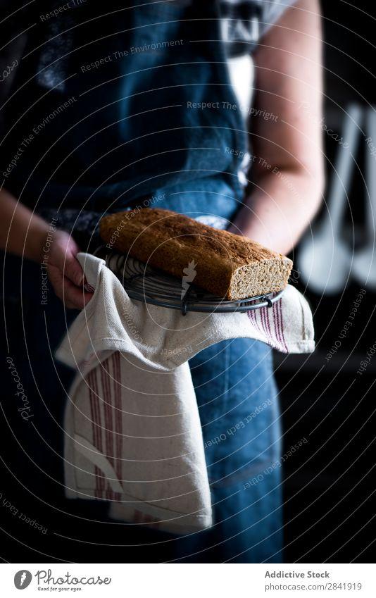 Frau, die einen selbstgemachten Kuchen mit Stoff hält. Küchenchef Halt Hand Dessert gebastelt Pasteten Lebensmittel frisch Scheibe Biskuit süß lecker Zucker