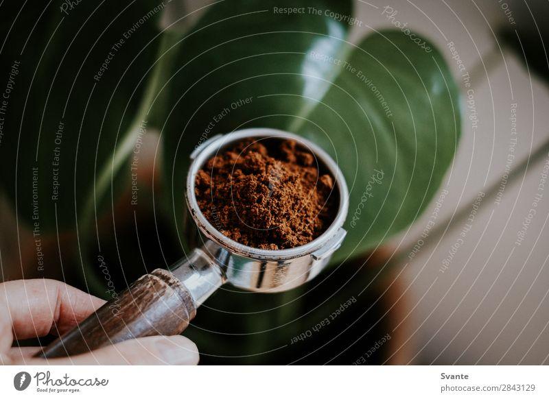 Nahaufnahme von Portafilter Kaffeetrinken Heißgetränk Latte Macchiato Espresso Lifestyle Berlin frisch Koffein gemahlener Kaffee Morgen vorbereitend Hand Halt
