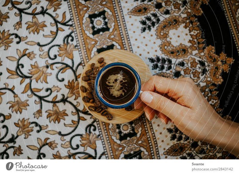 Frau hält Kaffeetasse auf floralem Muster fest Heißgetränk Kakao Latte Macchiato Espresso Tasse Becher Lifestyle Stil Design Mensch Junger Mann Jugendliche Hand