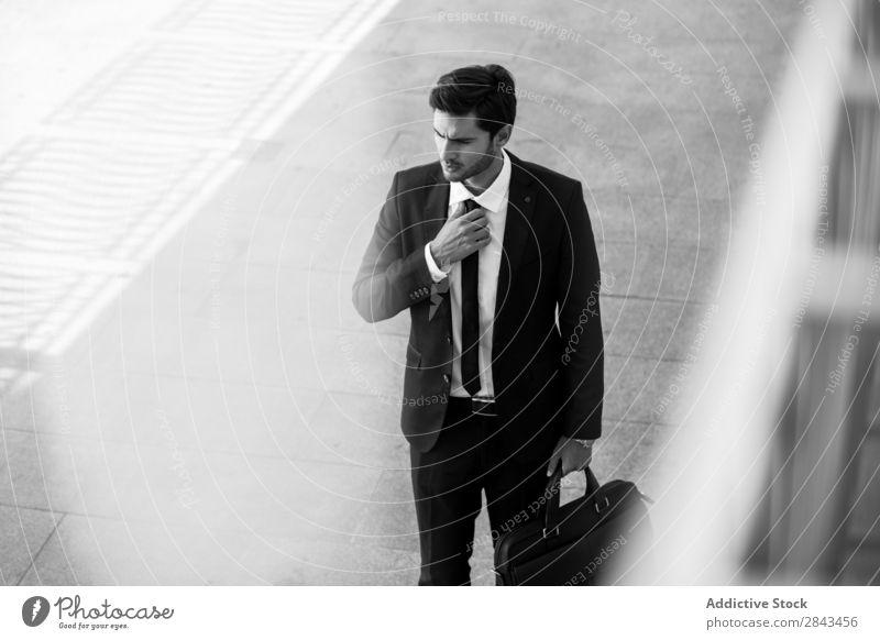 Ernsthafter Geschäftsmann mit Aktentasche, die Hand an der Krawatte hält. Straße schwarz-weiß ernst Porträt Wegsehen Halt besinnlich stehen Schwarzweißfoto
