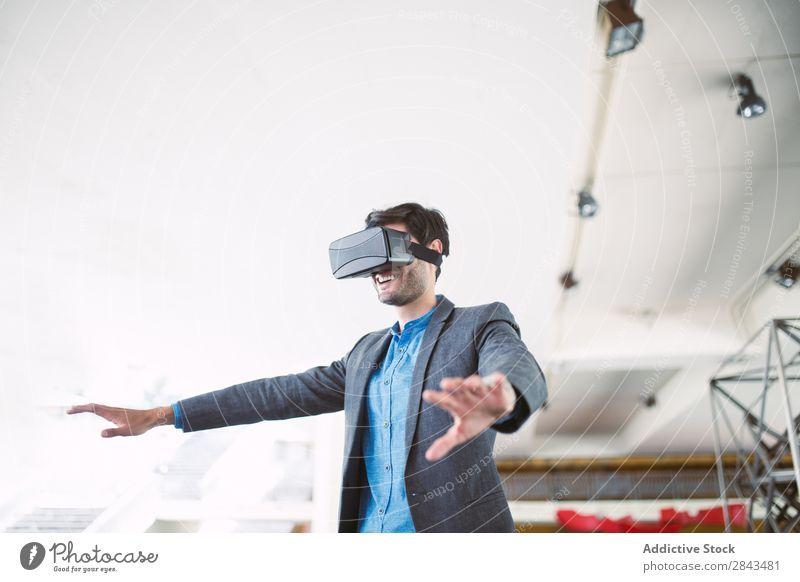 Ein Mann, der sich eine Virtual-Reality-Brille ansieht. Technik & Technologie cyber brünett Virtuelle Realität Kopf Anzeige Spielen realistisch Apparatur