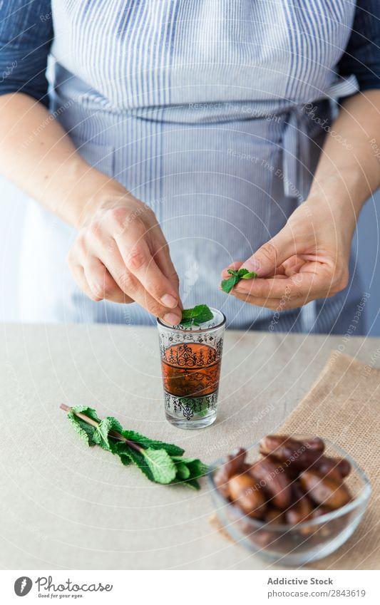 Pflanzenkoch mit Blättern in ein kleines Glas geben Koch Minze Zutaten duftig organisch kochen & garen frisch Kräuterbuch grün aromatisch Blatt Gesundheit
