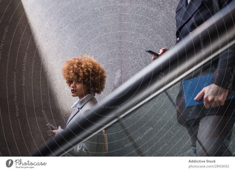 Stilvolles Paar mit Telefon auf der Rolltreppe Erwachsene schön PDA benutzend Mantel warme Kleidung Zusammensein gutaussehend hübsch Fröhlichkeit Freund