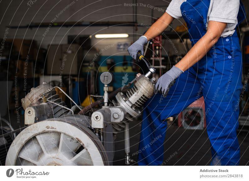 Mechanikerin, die einen Kompressormotor mit einem Schraubenschlüssel befestigt. Automechaniker Frau Porträt Reparatur Mitarbeiter industriell Lokomotive