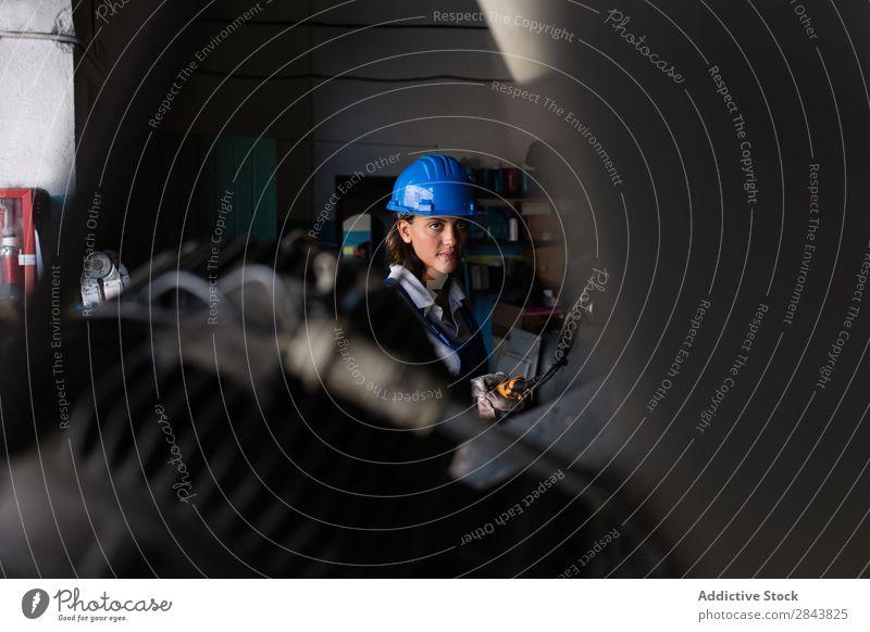 Mechanikerin, die ein Hebezeug zum Anheben eines Kompressormotors bedient. Automechaniker Frau Reparatur Mitarbeiter industriell Schutzhelm Lokomotive