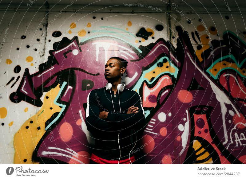 Selbstbewusster Mann posiert gegen Graffiti Körperhaltung einzigartig Stil Selbstständigkeit selbstbewußt schwarz Kopfhörer Großstadt Technik & Technologie