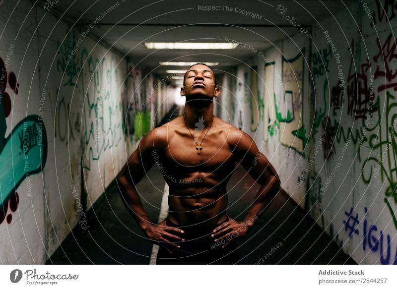 Fröhlicher Sportler, der unter Tage posiert. Mann schäbig sportlich Muskulatur zeigen ohne Hemd Afrikanisch Graffiti U-Bahn gutaussehend Torso Model Körper