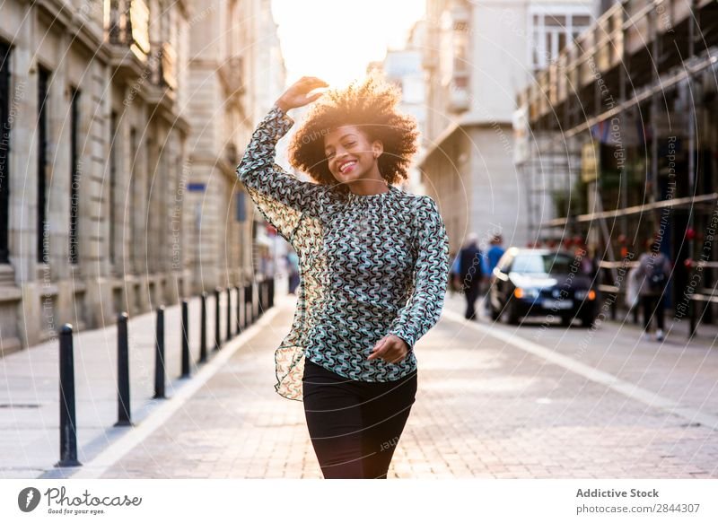 Fröhliche ethnische Frau, die auf der Straße spazieren geht. Fröhlichkeit träumen Stadt laufen Erfolg Stil romantisch Beautyfotografie feminin Körperhaltung