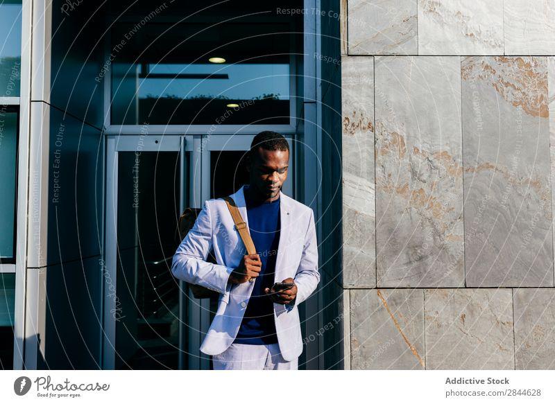 Zufriedener, stilvoller Mann mit Handy in der Innenstadt Stil Straße PDA Großstadt Internet Technik & Technologie Erfolg beobachten Mitteilung Afrikanisch Mode
