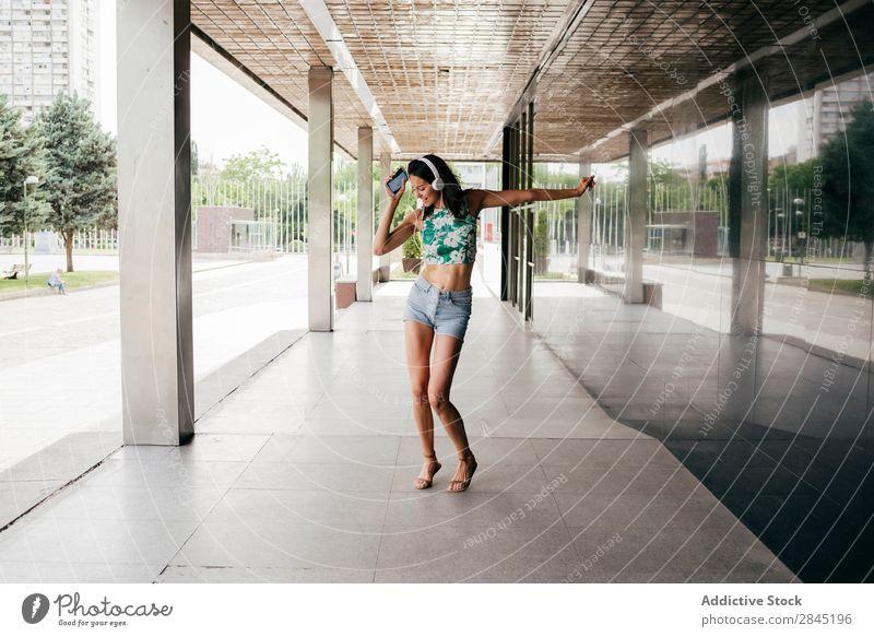 Hübsche Frau tanzt in Kopfhörern. Musik PDA Tanzen Straße Großstadt Stadt Mädchen Jugendliche Telefon Lifestyle schön Technik & Technologie Glück Mobile Lächeln