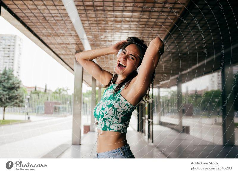 Ausdrucksstarke Frau, die in Kopfhörern tanzt. Musik Tanzen Aufregung expressiv Straße Großstadt Stadt Mädchen Jugendliche Telefon Lifestyle schön