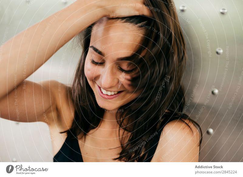 Sinnliche Frau, die das Haar berührt. hübsch Lächeln genießen Behaarung berühren Augen geschlossen ausrichten schön Glück Porträt Mädchen Metall Wand